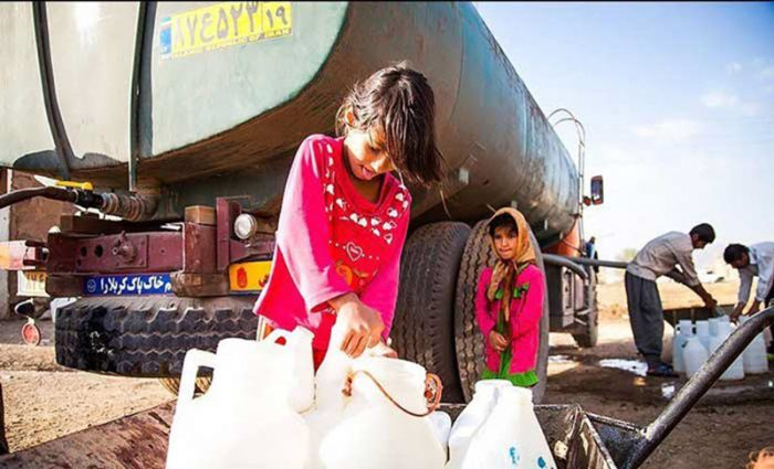 Drought-A girl using water containers to take water home