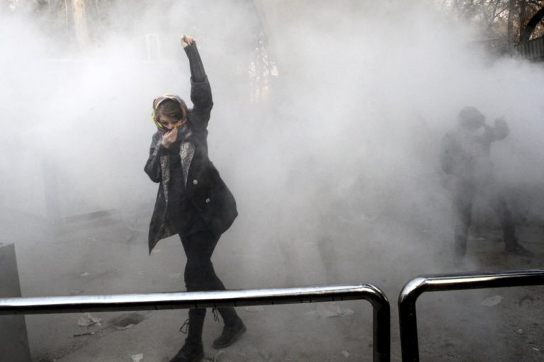 The protester that raises her arm as a symbol of resistance, while stepping out of teargas