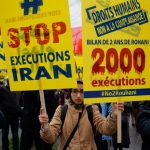 "MEK supporters holding signs reading ""Stop Executions Iran"""