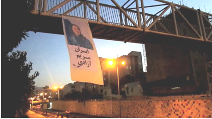 Hanging a large banner carrying Mrs. Maryam Rajavi's picture, by a MEK resistance unit, Niavaran Highway, Tehran5